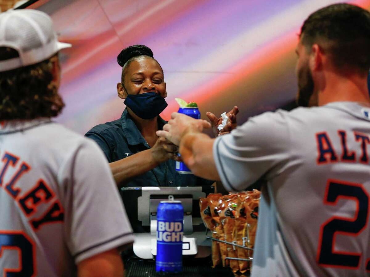 Katrelle Gabriel, center, hands off a pair of beers to a customer before game 2 of the American League Division Series between the Houston Astros and the Chicago White Sox at Minute Maid Park on Friday, Oct. 8, 2021, in Houston.