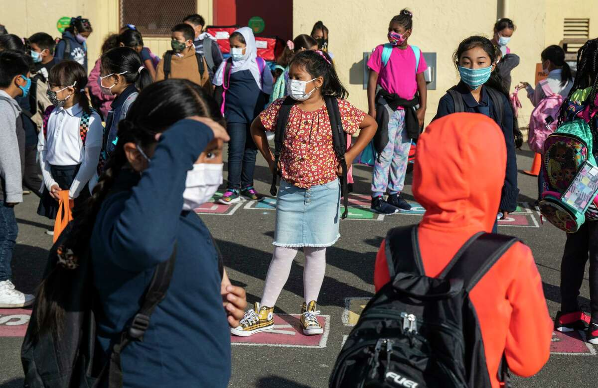 Students line up at Garfield Elementary School in Oakland. Mask mandates will probably stay until most are vaccinated.