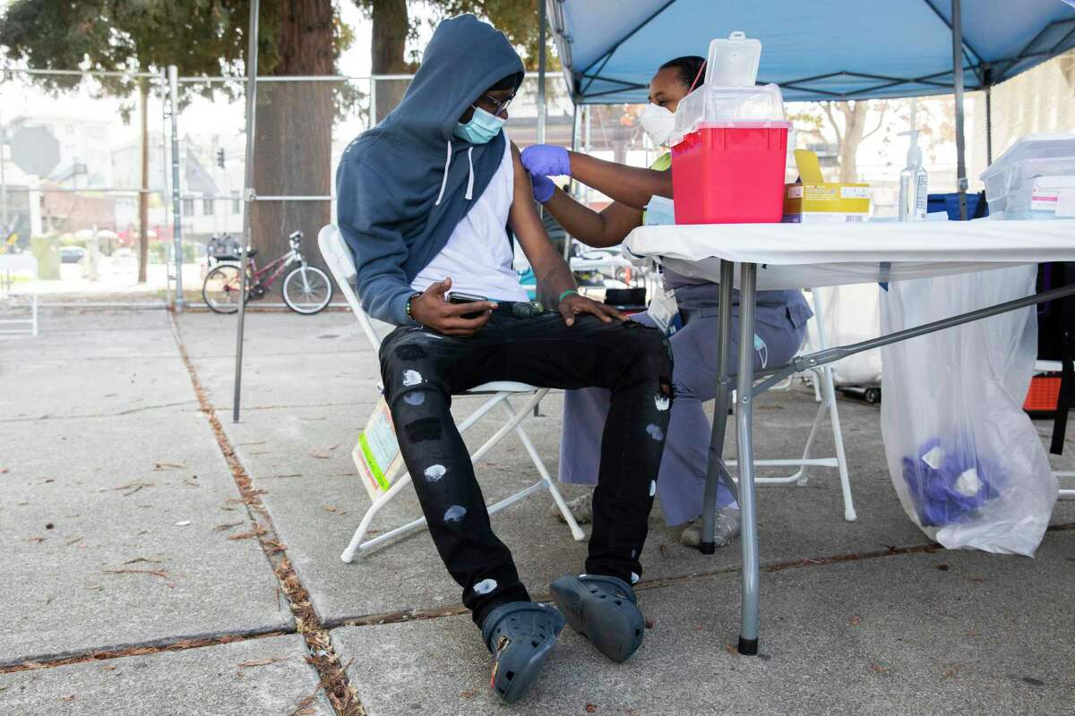Alameda County Public Health nurse Emawayish Haile administers the Pfizer vaccine to 17-year-old Oakland Tech student Daylon Perkins at a vaccine clinic at Oakland Tech High School in Oakland in September.