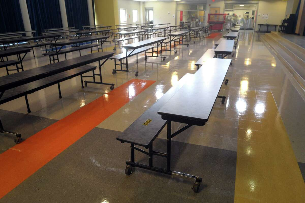 Cafeteria tables have been cut half at Johnson School so that students will all sit facing in one direction, seen here in Bridgeport, Conn. Aug. 27, 2020.