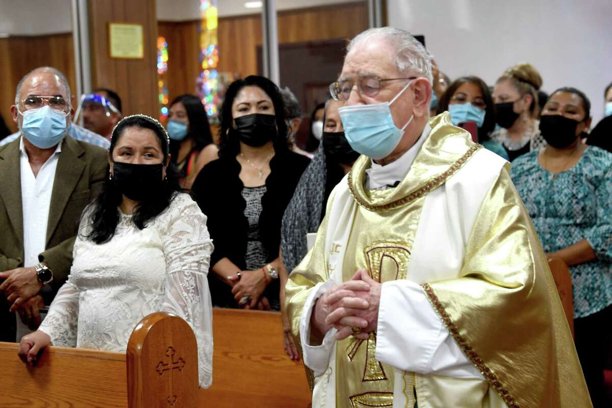 The. congregation stands during a mass celebrating the 100th birthday of Father Luis Urriza at Cristo Rey Catholic Church. Photo made Thursday, August 19, 2021 Kim Brent/The Enterprise