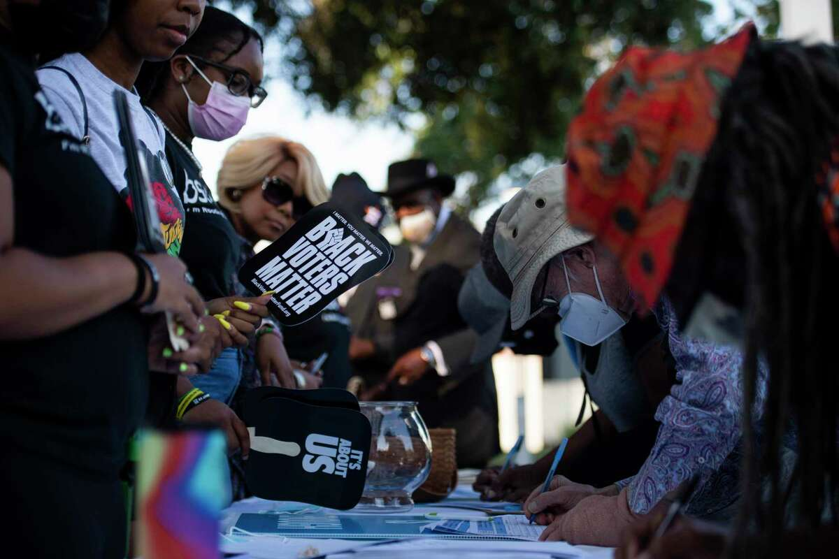 Members from the University of Houston Black Student Union sign in attendees of a rally against the redistricting efforts in Austin on Thursday, Oct. 7, 2021, at Emancipation Park in Houston, Texas.