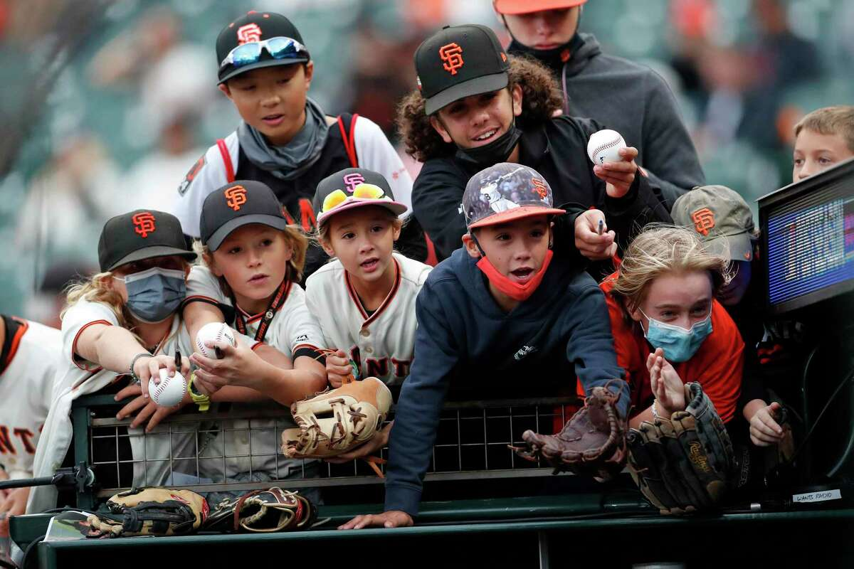 Young San Francisco Giants fans try to get the attention of a player before the game against the L.A. Dodgers at Oracle Park.