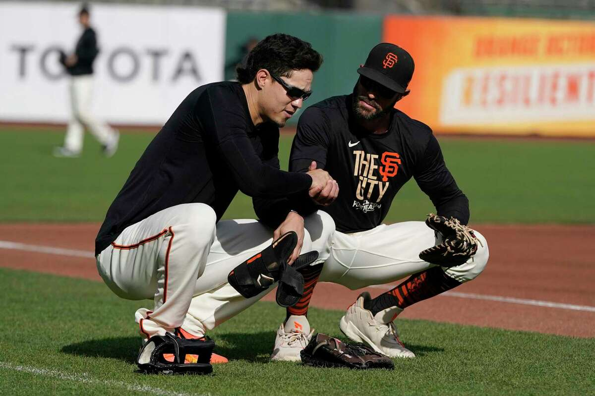 San Francisco Giants' Wilmer Flores, left, talks with manager Gabe Kapler during a baseball practice in San Francisco, Tuesday, Oct. 5, 2021. (AP Photo/Jeff Chiu)