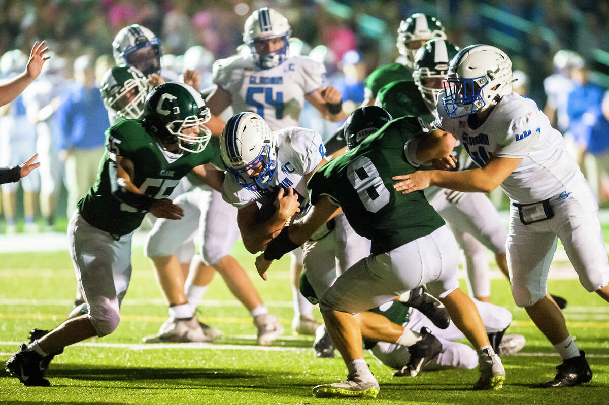 Gladwin's Logan Kokotovich, center, pushes through a line of defenders to score a touchdown in the second quarter of a game against Clare Friday, Oct. 8, 2021 in Clare. Due to early press deadlines, tonight's football coverage is available online at www.ourmidland.com and will appear in Monday's print edition. (Katy Kildee/kkildee@mdn.net)