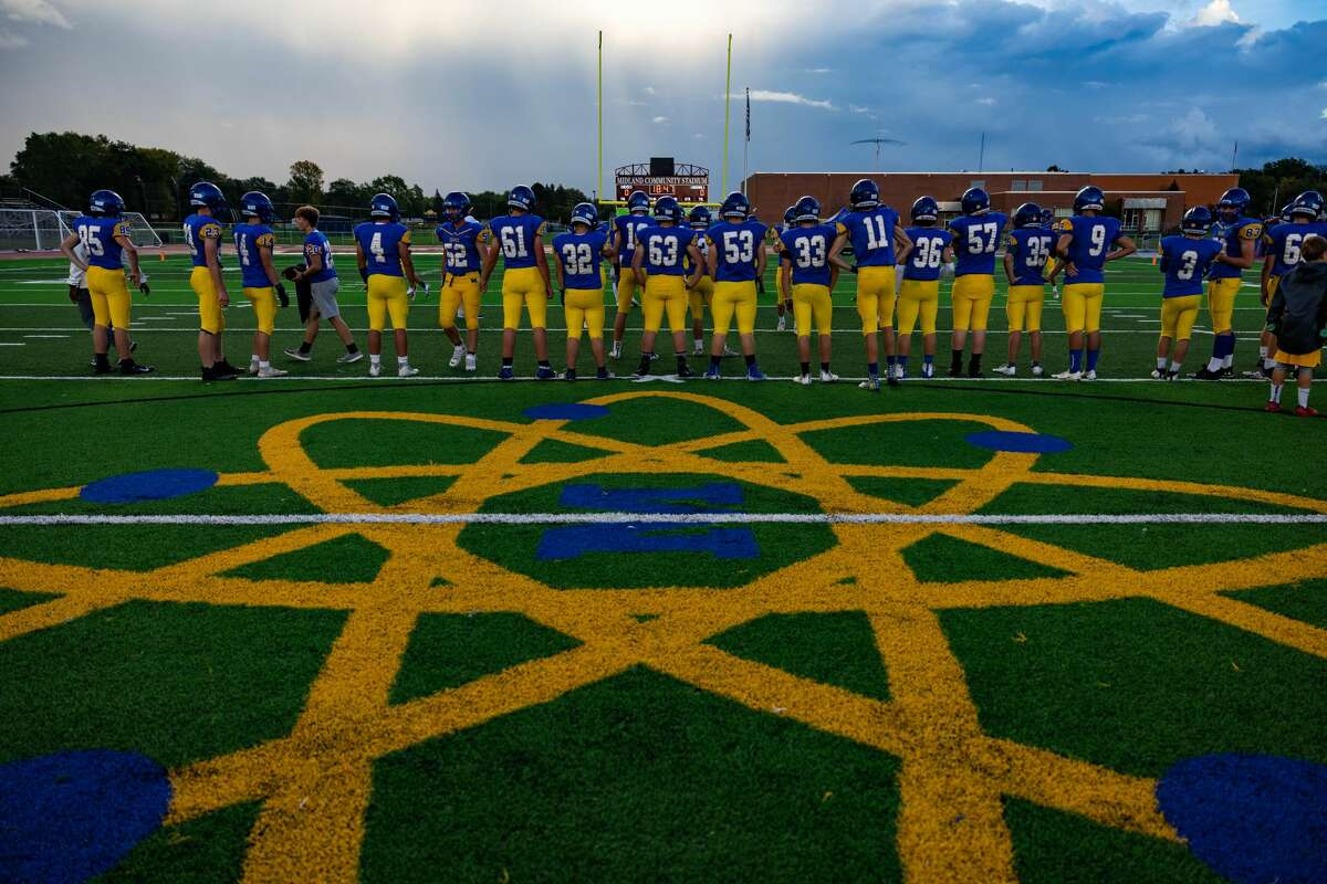 The Chemics line up near midfield as the team warms up before their game against Davison Friday, Oct. 8, 2021 at Midland Community Stadium. (Drew Travis/for the Daily News)