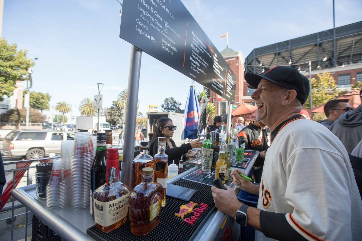 Patrick Nuck, right, shares a laugh with a bartender while paying for drinks at MoMo's Outdoor Patio Bar, a sports bar and restaurant across from Oracle Park in San Francisco on October 8, 2021.