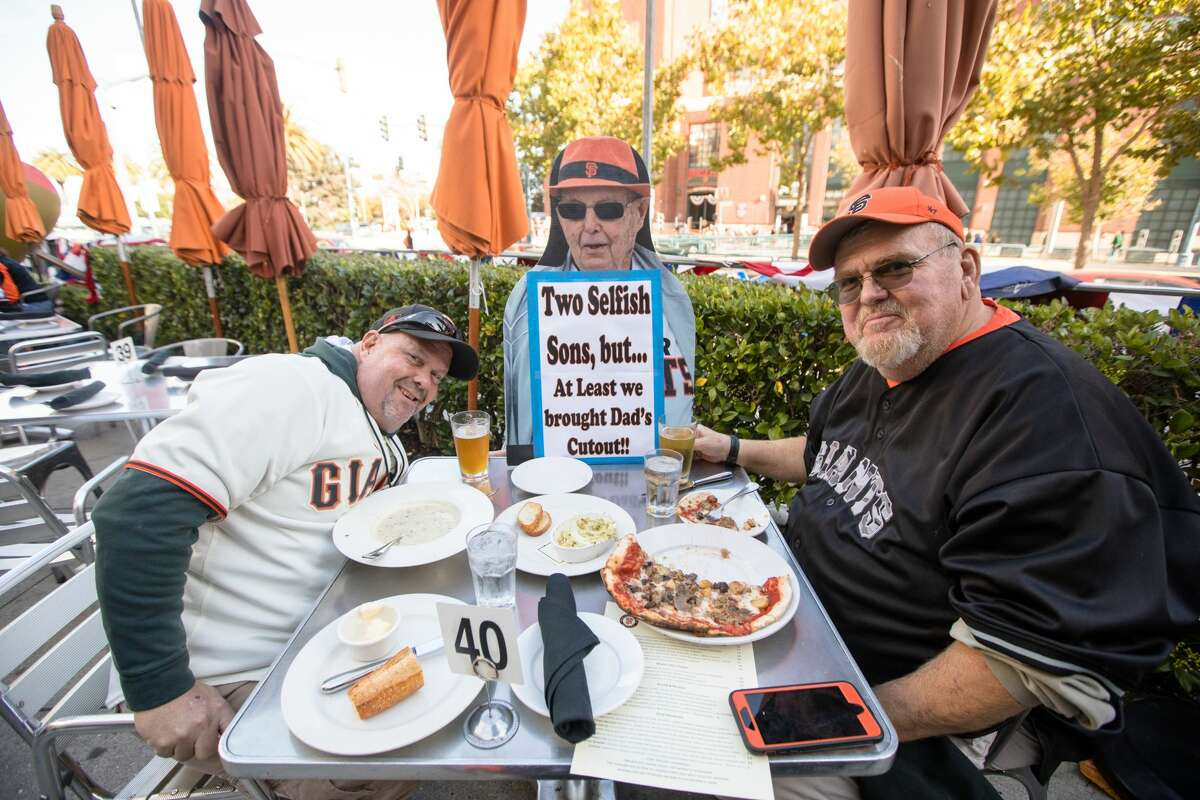 A cutout of Bert Crosthwaite, center, at the table with sons Ron, left, and Jim as they enjoy a pre-game meal at MoMo's.  The Sacramento-area Crosthwaites love to go to Giants games, but Bert couldn't make it to that game.  Instead, his sons brought a cutout that was inside Oracle Park during the 2020 pandemic season.