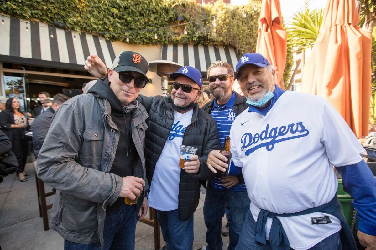 (Left to Right) San Francisco Giants fan Chris Sammet chats with Los Angeles Dodgers fans Dan Cota, Steve Quinn and Henry Eshom at Momo Sports Bar and Restaurant across from Oracle Park in San Francisco on October 8, 2021.