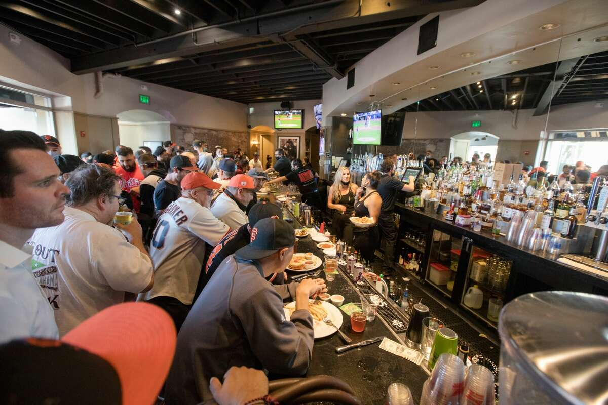 San Francisco Giants fans sit at the bar at MoMo's, a sports bar and restaurant across from Oracle Park in San Francisco on October 8, 2021, ahead of Game 1 of the National League Division Series.