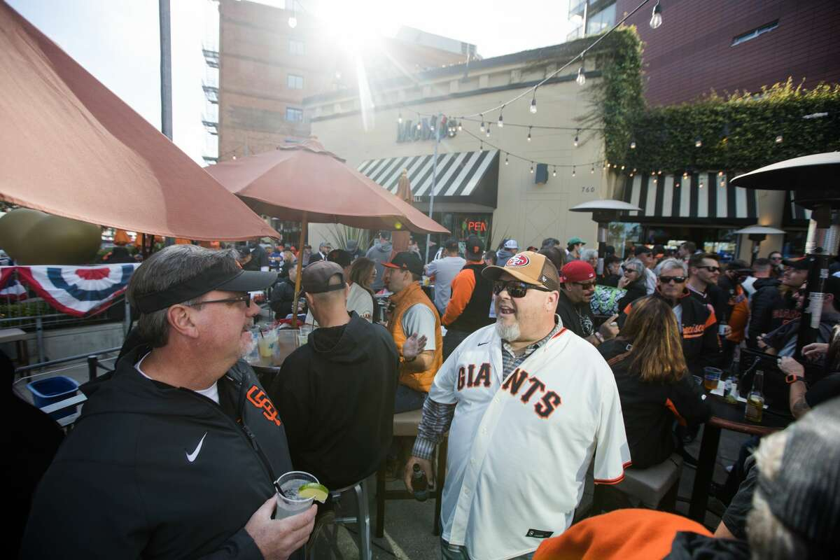 San Francisco Giants fans Vic Gets, left, and Jeff Markley, center, enjoy drinks on MoMo's crowded outdoor patio on October 8, 2021, ahead of the National League Division Series opener.