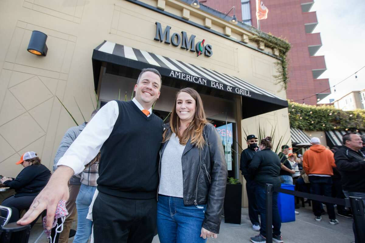 MoMo owner Scott Morton poses with his wife Caitlyn outside their sports bar and restaurant, which is across from Oracle Park in San Francisco.