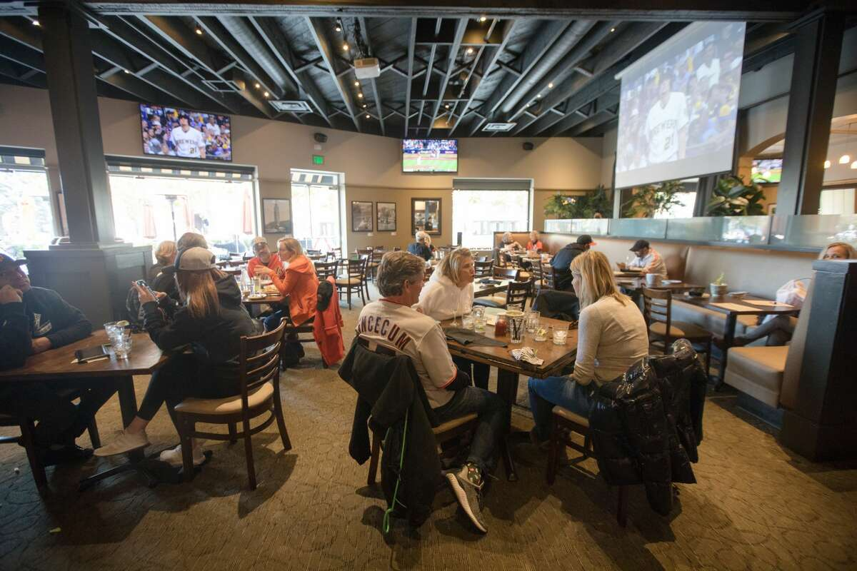 Giants fans enjoy a pre-game meal at MoMo's, a sports bar and restaurant across from Oracle Park in San Francisco on October 8, 2021.