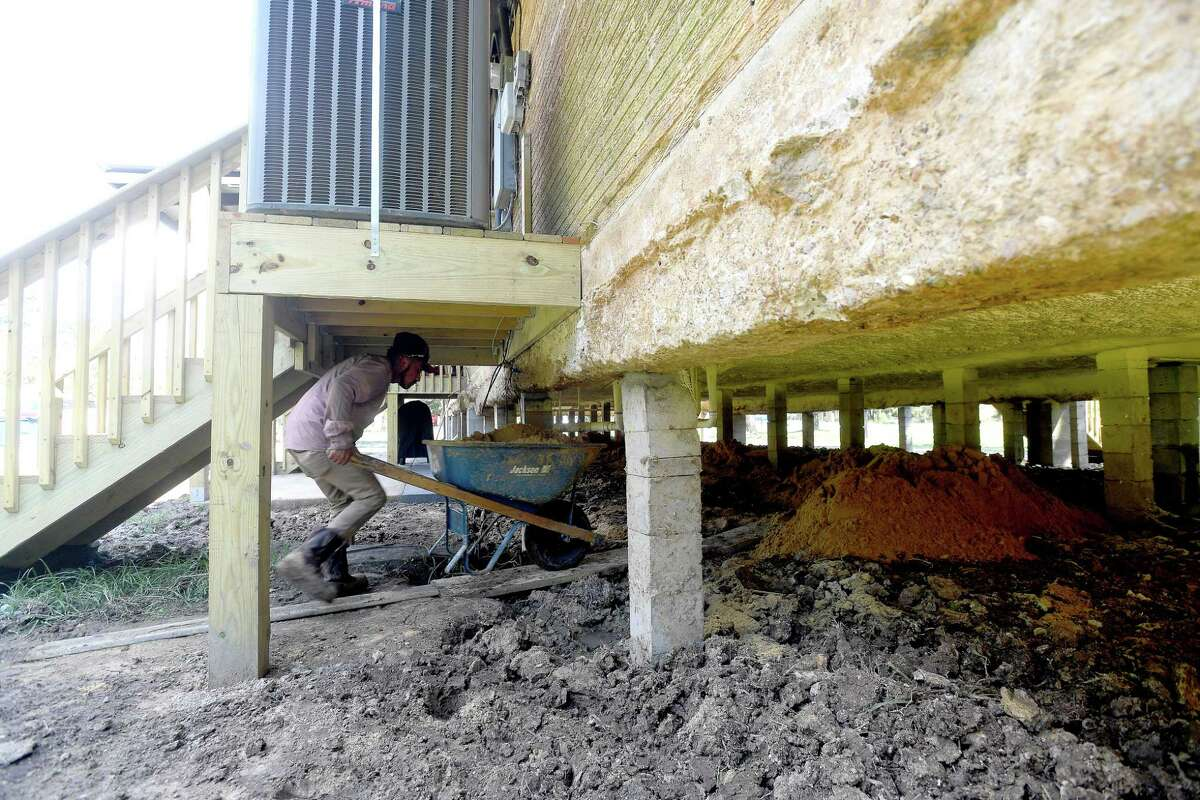 A worker moves cartloads of dirt beneath a raised home as the ground surrounding it is leveled. Several homes in Bevil Oaks have been raised, with many more scheduled for elevation work, following grant money to do the work as protection against future flood damage. Residents in the small city straddling the Jefferson and Hardin County line were among some of the hardest hit during Tropical Storm Harvey. Photo made Wednesday, October 6, 2021 Kim Brent/The Enterprise