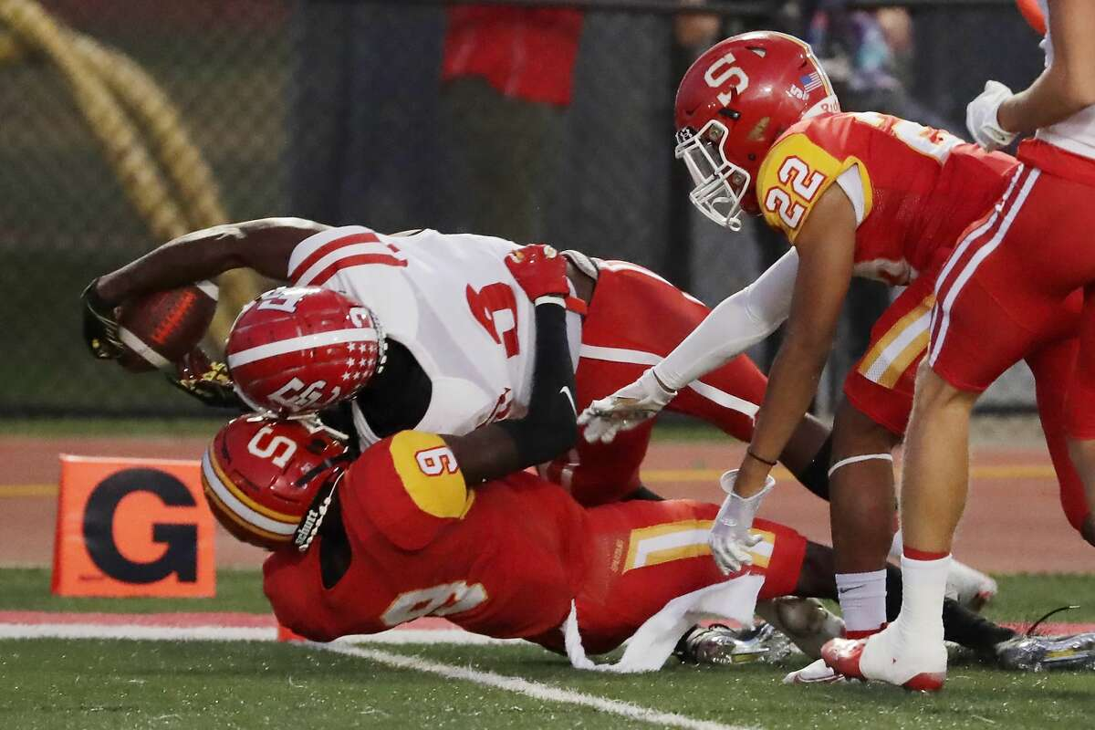 El Campo running back Johntri Davis, top left, stretches for the touchdown over Stafford defenders Chase Williams (9) and Ashton Miller (22) during the first half of a high school football game Friday, Oct. 8, 2021 in Houston, TX.