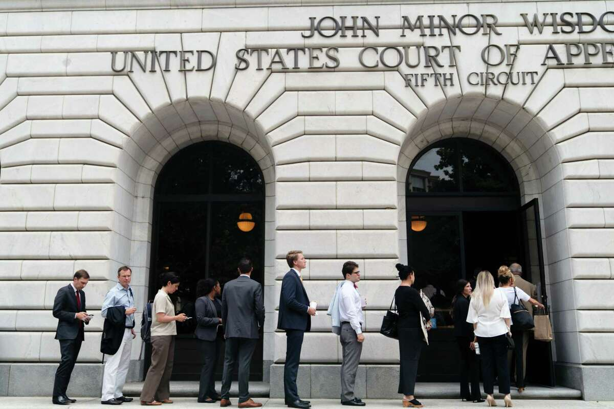 FILE -- Spectators line up on July 9, 2019, to watch oral arguments in Texas v. U.S. at the United States Court of Appeals for the Fifth Circuit in New Orleans. The court on Wednesday, Nov. 18, 2019, struck down a central provision of the Affordable Care Act, ruling that the requirement that people have health insurance was unconstitutional. (Annie Flanagan/The New York Times)