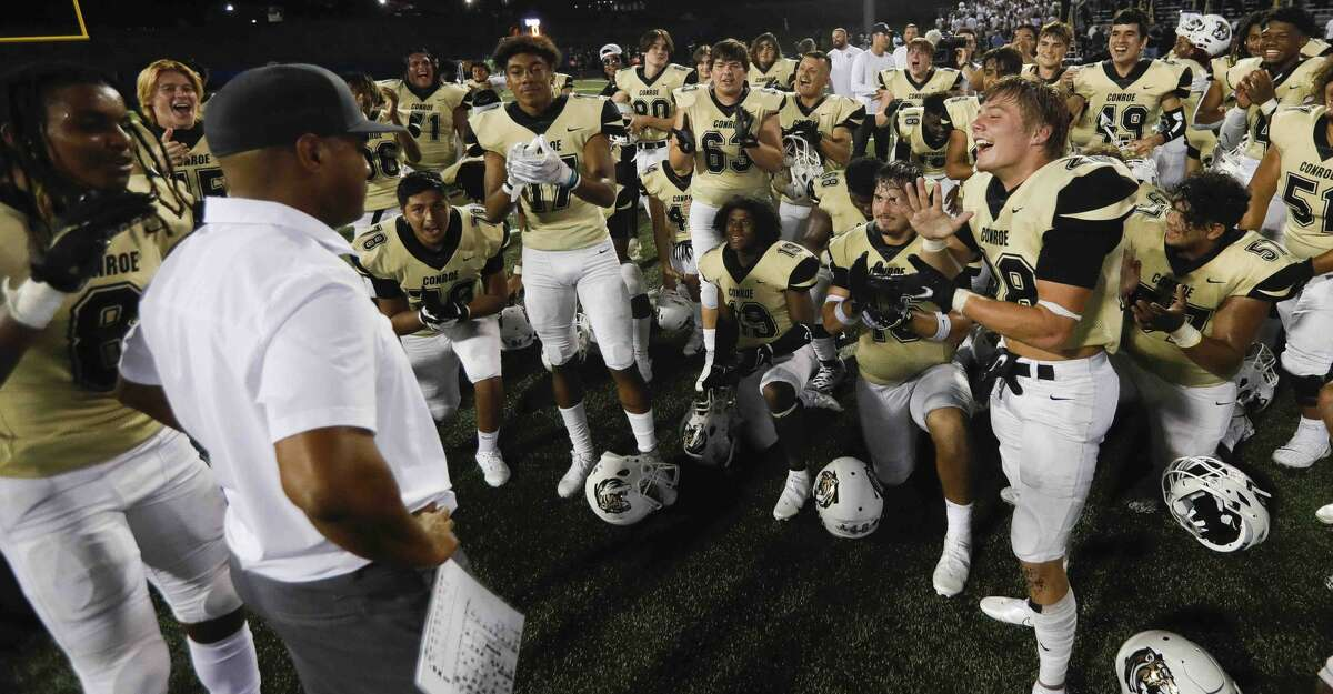 Conroe head coach Cedric Hardeman receives a standing ovation from his players after defeating Oak Ridge 44-41 on homecoming during a District 13-6A high school football game at Buddy Moorhead Stadium, Friday, Oct. 8, 2021, in Conroe.