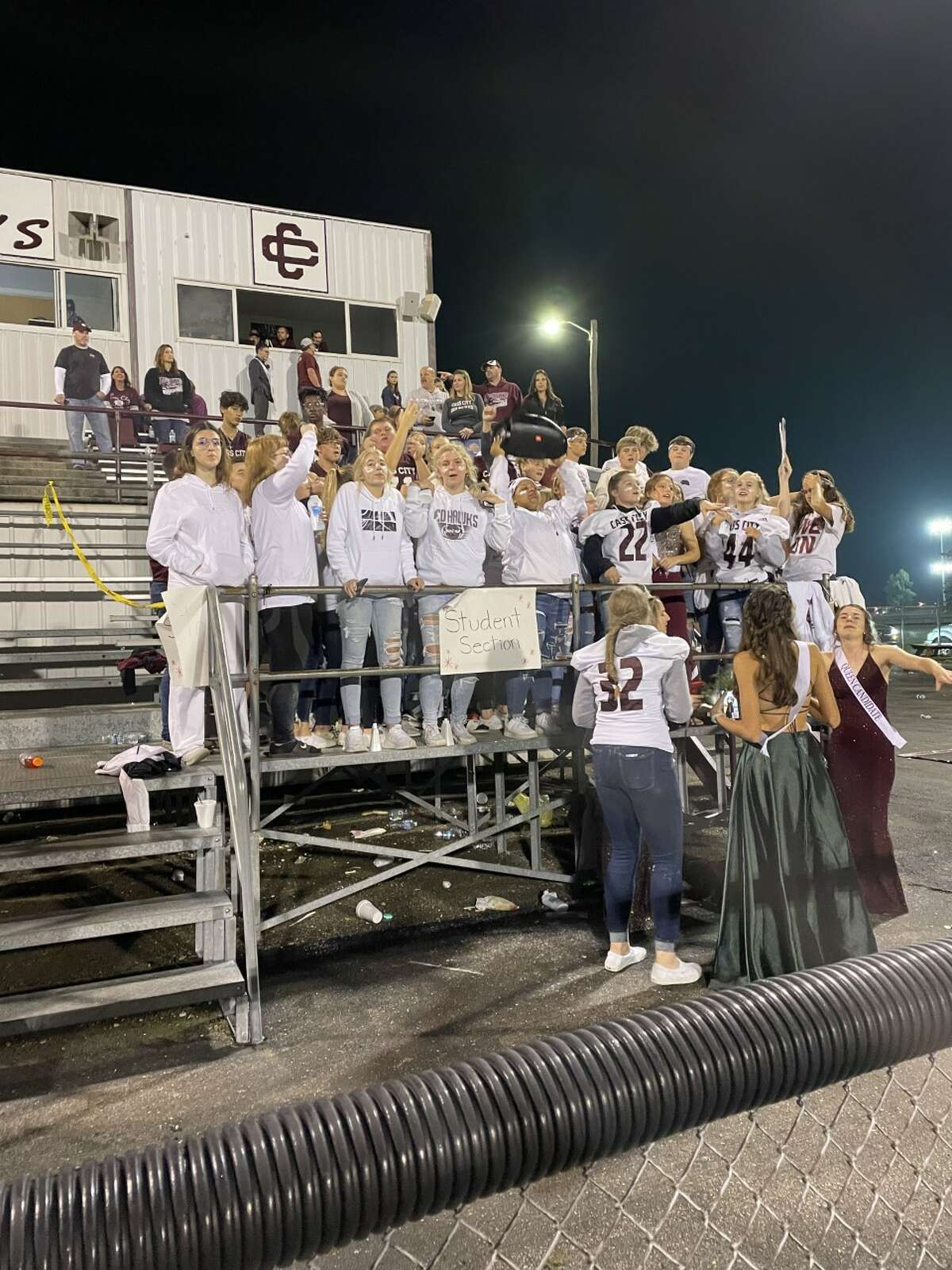 The Cass City student section dances to music during the lightning delay.