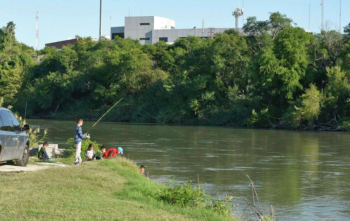 A family fishes on the banks of the Rio Grande, the border between the United States and Mexico, on Saturday, Nov. 3, 2018 at Tres Laredos Park in Laredo, Texas.