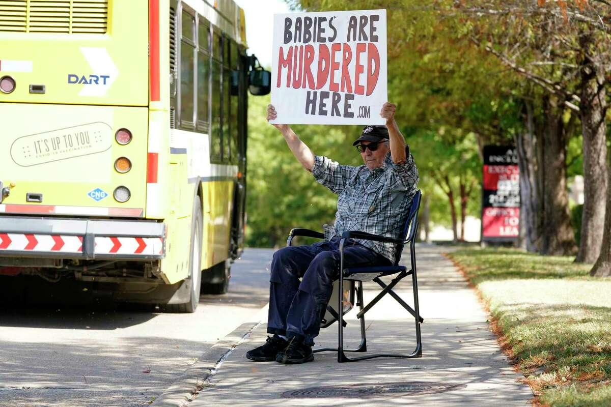 """David Trujillo sostiene un letrero frente a una construcción donde opera un proveedor de abortos el jueves 7 de octubre de 2021, en Dallas, Texas. El letrero dice: """"Aquí se asesina a bebés""""."""