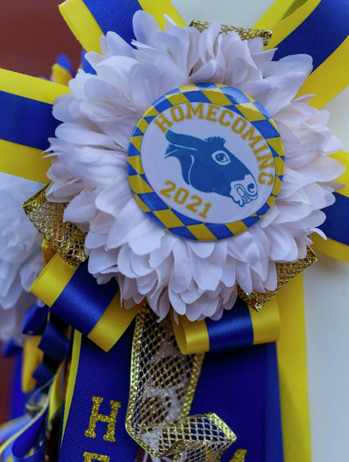 A homecoming mum is seen Friday, Oct. 8, 2021 on a cheerleader's megaphone before the start of the Alamo Heights Mules' homecoming game against Floresville.