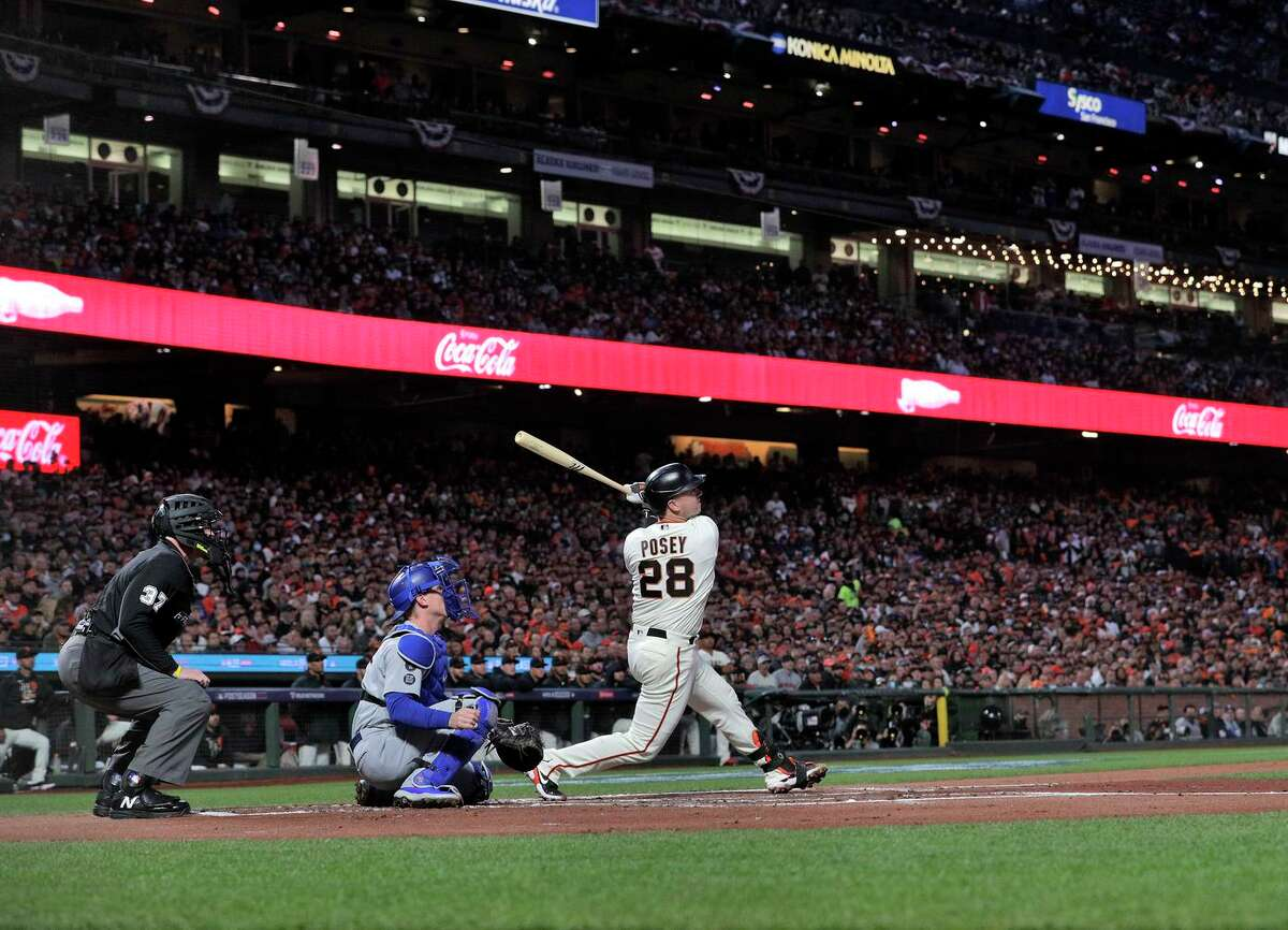 Above: Buster Posey hits a two-run home run to right field in the first inning. Below: Tommy La Stella (right) and Brandon Crawford start a spectacular double play in the fourth.