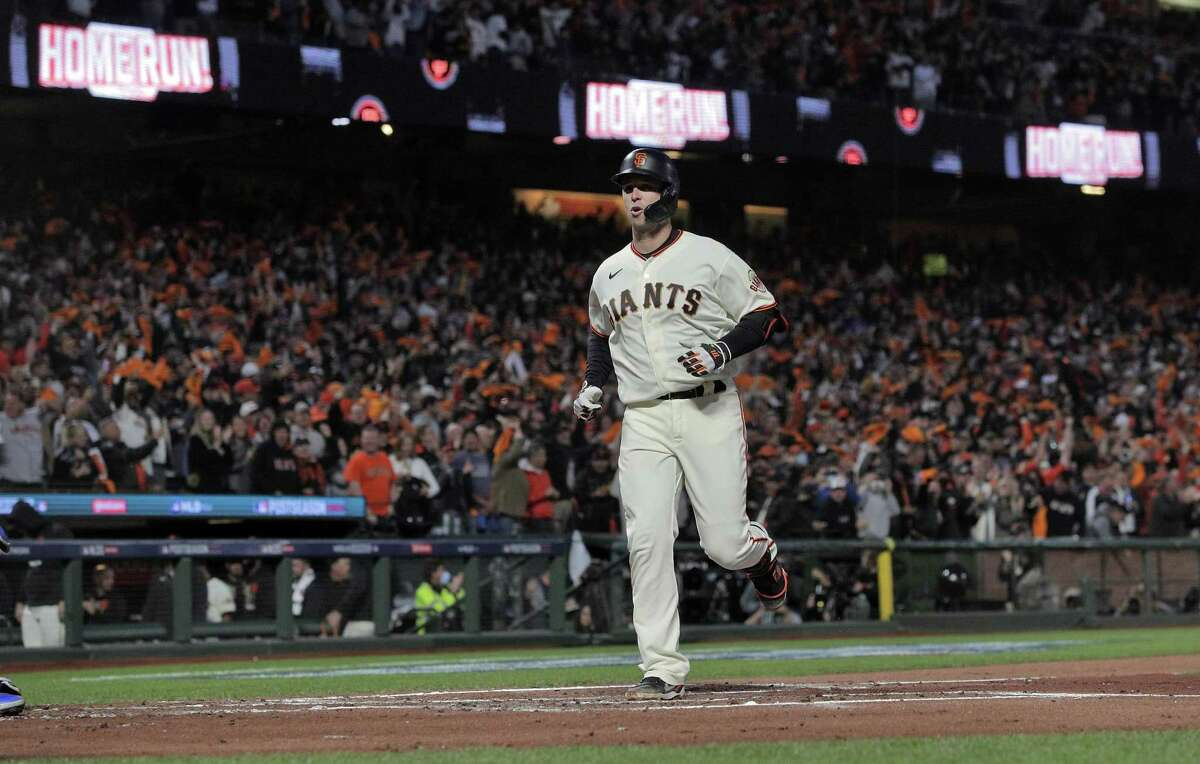 Buster Posey (28) approaches homeplate after hitting a two run homerun in the first inning as the San Francisco Giants played the Los Angeles Dodgers in Game 1 of the National League Division Series at Oracle Park in San Francisco, Calif., on Friday, October 8, 2021.