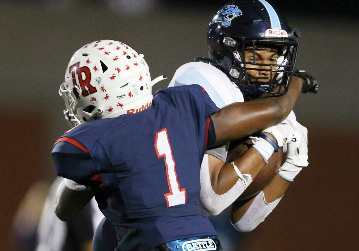 Johnson's Alejandro Tavares (11) makes a catch against Roosevelt's DeShawn Washington (01) during their football game at Heroes Stadium on Friday, Oct. 8, 2021.