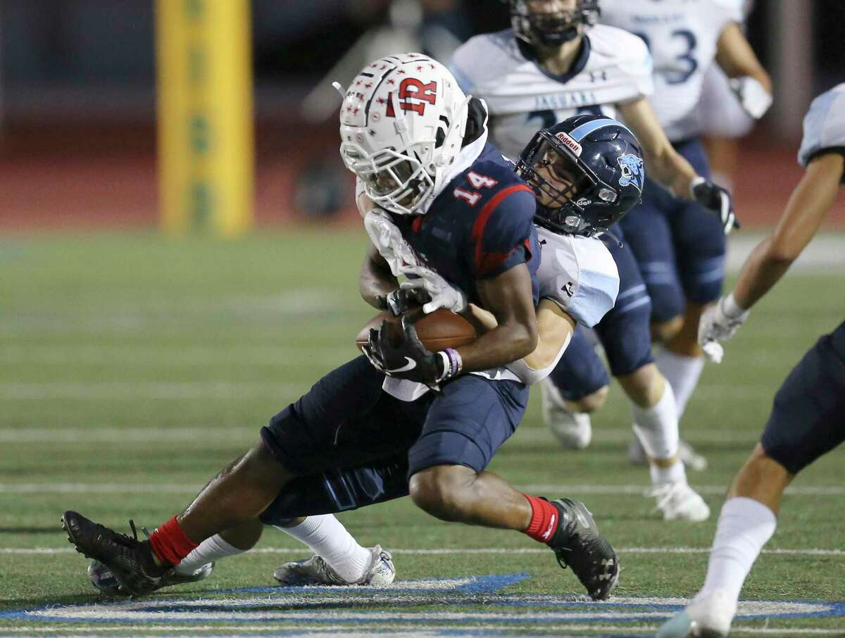 Roosevelt's Andrew Price (14) holds onto the ball against Johnson's Darren Benavides (34) during their football game at Heroes Stadium on Friday, Oct. 8, 2021.