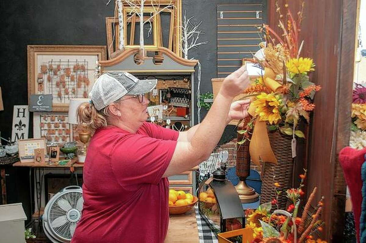 MacKenzie Gieseke of Square Trade at 10 E. Cross St. arranges a store display Friday afternoon in preparation for weekend shoppers.