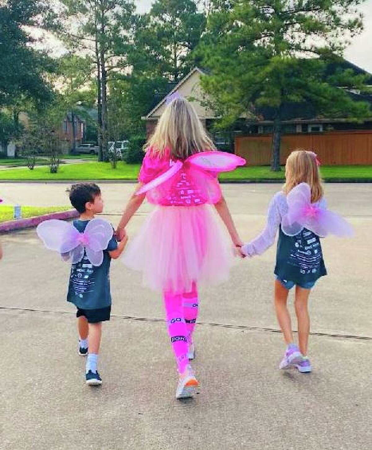Victoria Simo holds her children's hands as they walk in her studio's 2021 Susan G. Komen Race for the Cure event on Saturday, Oct. 2, in northwest Houston.
