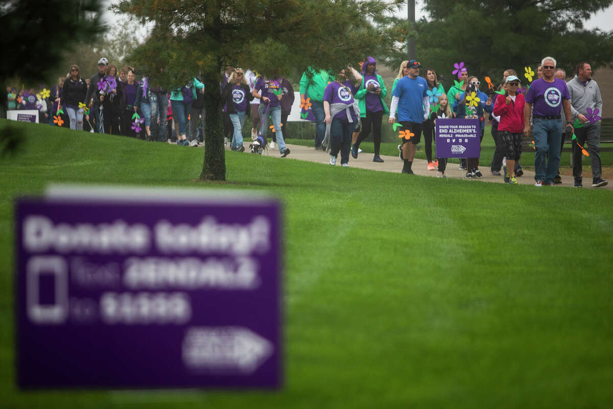 Hundreds of people participate in the Walk to End Alzheimer's Saturday, Oct. 9, 2021 at Dow Diamond in Midland. The group began at Dow Diamond, and planned to walk to the Tridge and back to raise awareness and funds for the Alzheimer's care and research. (Katy Kildee/kkildee@mdn.net)