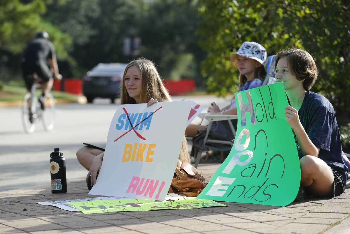 Kayla Fuller, left, and her sister, Tory, holds signs and cheer on athletes as they compete in the Ironman Triathlon, Saturday, Oct. 9, 2021, in The Woodlands.