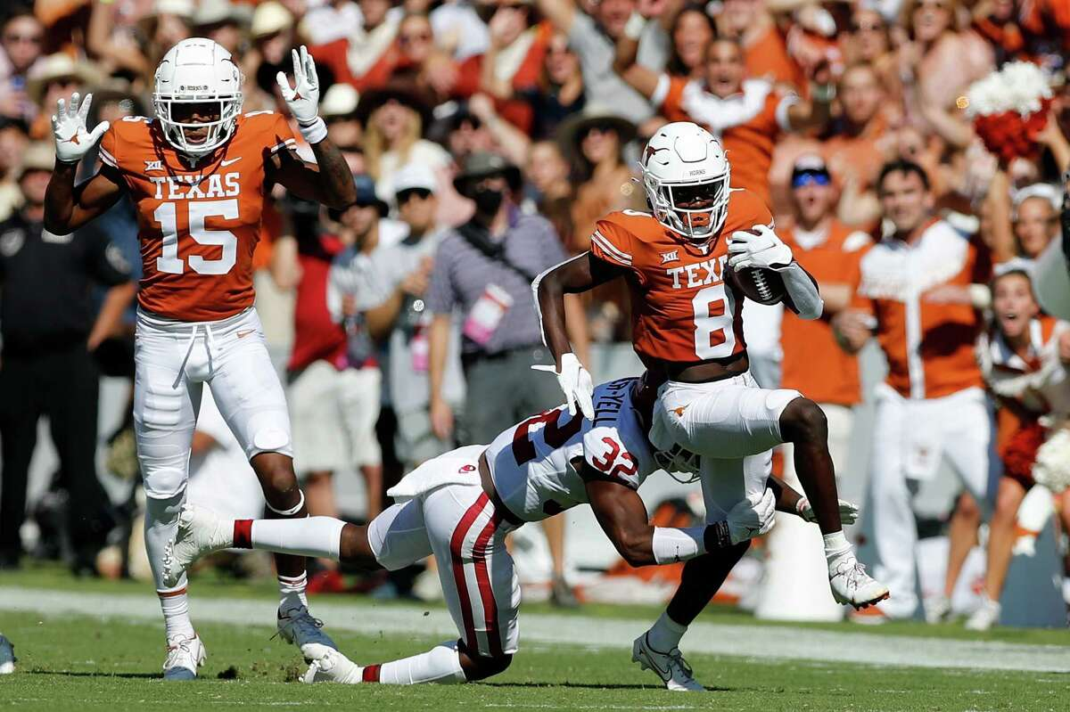 DALLAS, TEXAS - OCTOBER 09: Xavier Worthy #8 of the Texas Longhorns catches a pass and breaks the tackle by Delarrin Turner-Yell #32 of the Oklahoma Sooners for a touchdown in the first quarter during the 2021 AT&T Red River Showdown at Cotton Bowl on October 09, 2021 in Dallas, Texas.