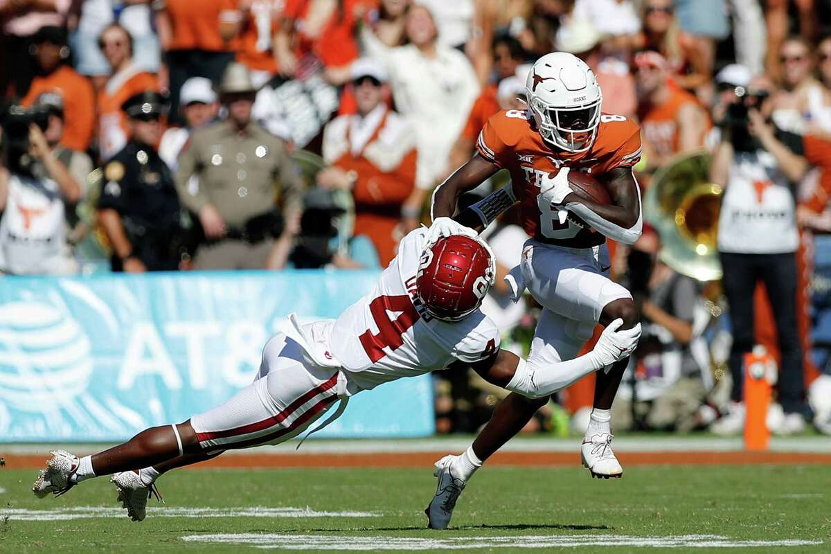 DALLAS, TEXAS - OCTOBER 09: Xavier Worthy #8 of the Texas Longhorns gives a stiff arm to Jaden Davis #4 of the Oklahoma Sooners and runs for a touchdown in the first quarter during the 2021 AT&T Red River Showdown at Cotton Bowl on October 09, 2021 in Dallas, Texas.