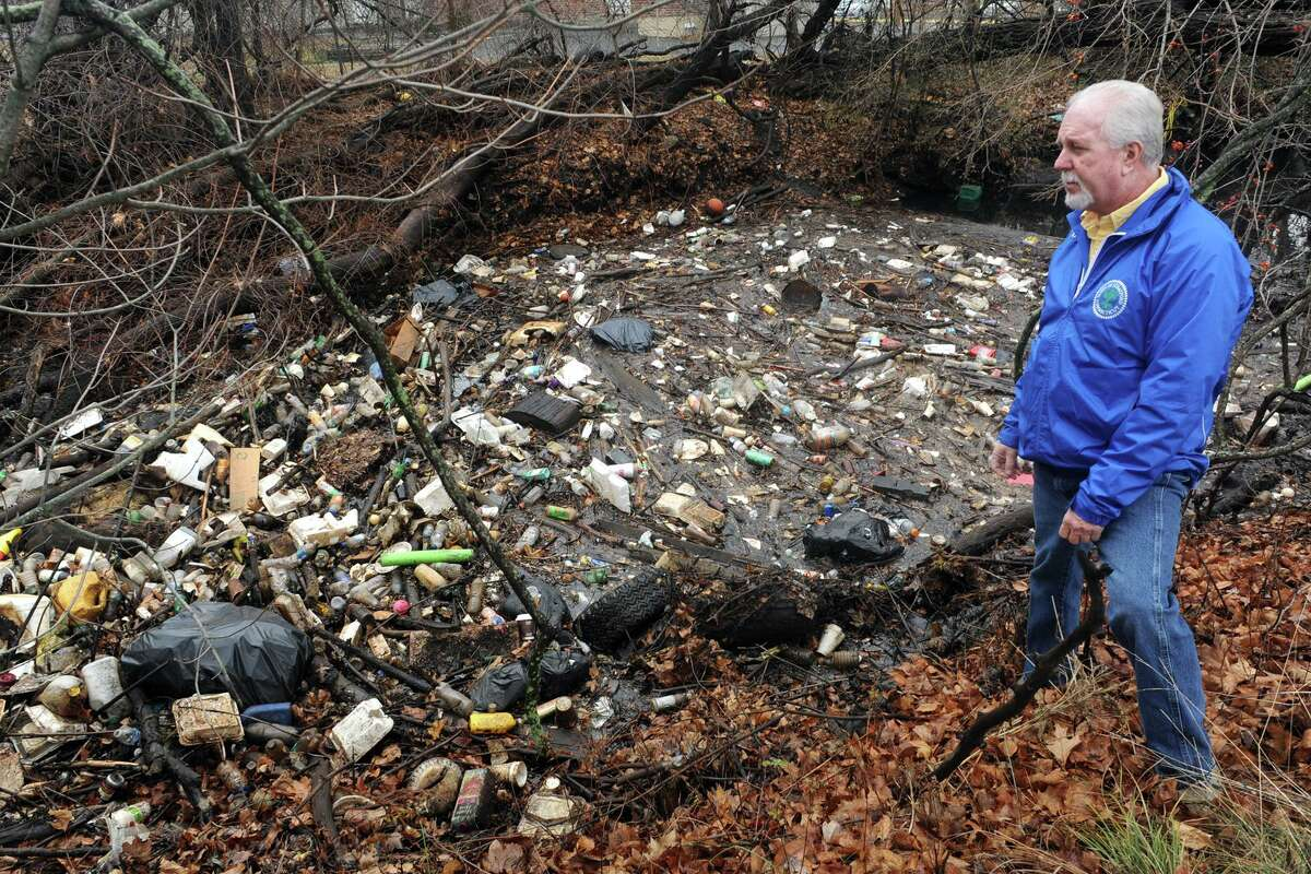 A December 2016 file photo showing Rich Fredette, blight control officer for the Town of Stratford, at Bruce Brook, clogged with trash and debris.