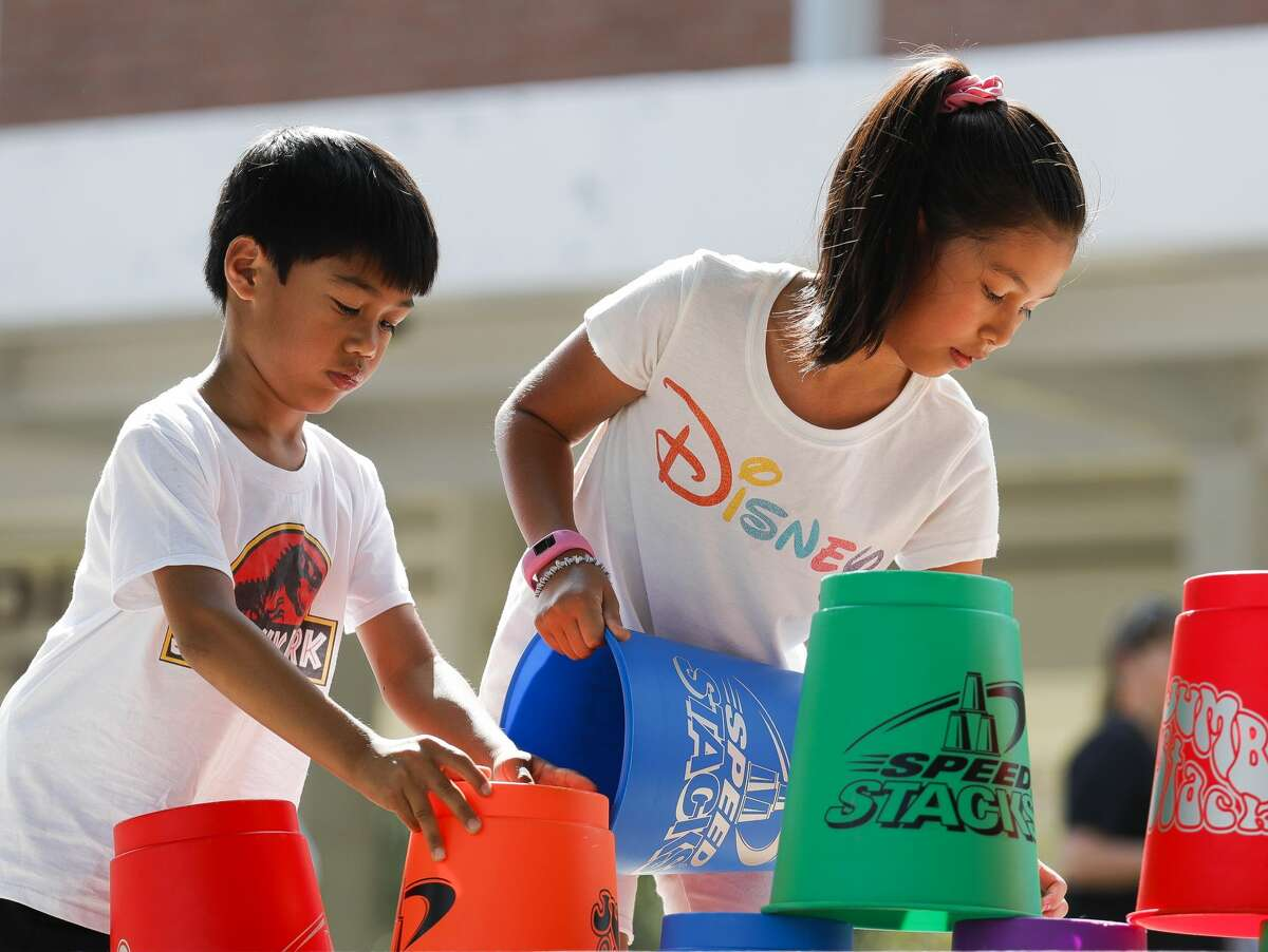 Lilly Anib stacks up mugs in a game alongside her brother, Collin, during the annual Conroe Cajun Catfish Festival on Saturday, October 9, 2021, in Conroe.