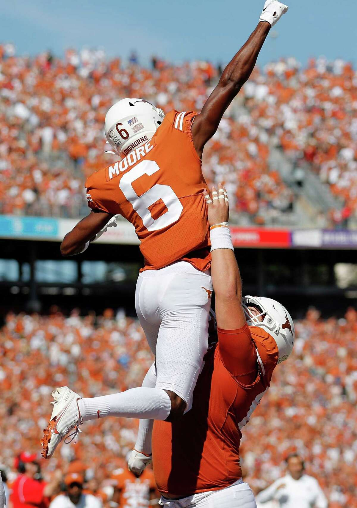 DALLAS, TEXAS - OCTOBER 09: Jake Majors #65 of the Texas Longhorns celebrates with Joshua Moore #6 after a touchdown reception in the first quarter against the Oklahoma Sooners during the 2021 AT&T Red River Showdown at Cotton Bowl on October 09, 2021 in Dallas, Texas.