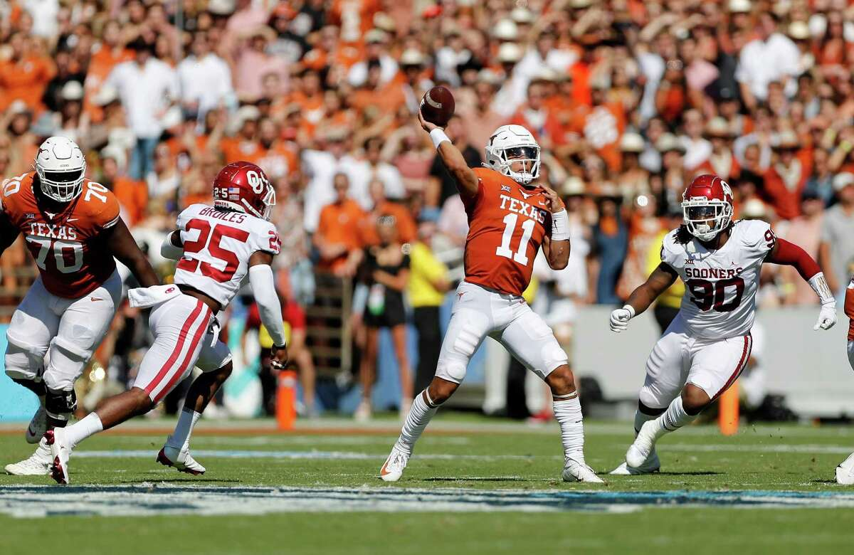 DALLAS, TEXAS - OCTOBER 09: Casey Thompson #11 of the Texas Longhorns looks to pass under pressure by Josh Ellison #90 of the Oklahoma Sooners and Justin Broiles #25 in the first quarter during the 2021 AT&T Red River Showdown at Cotton Bowl on October 09, 2021 in Dallas, Texas.