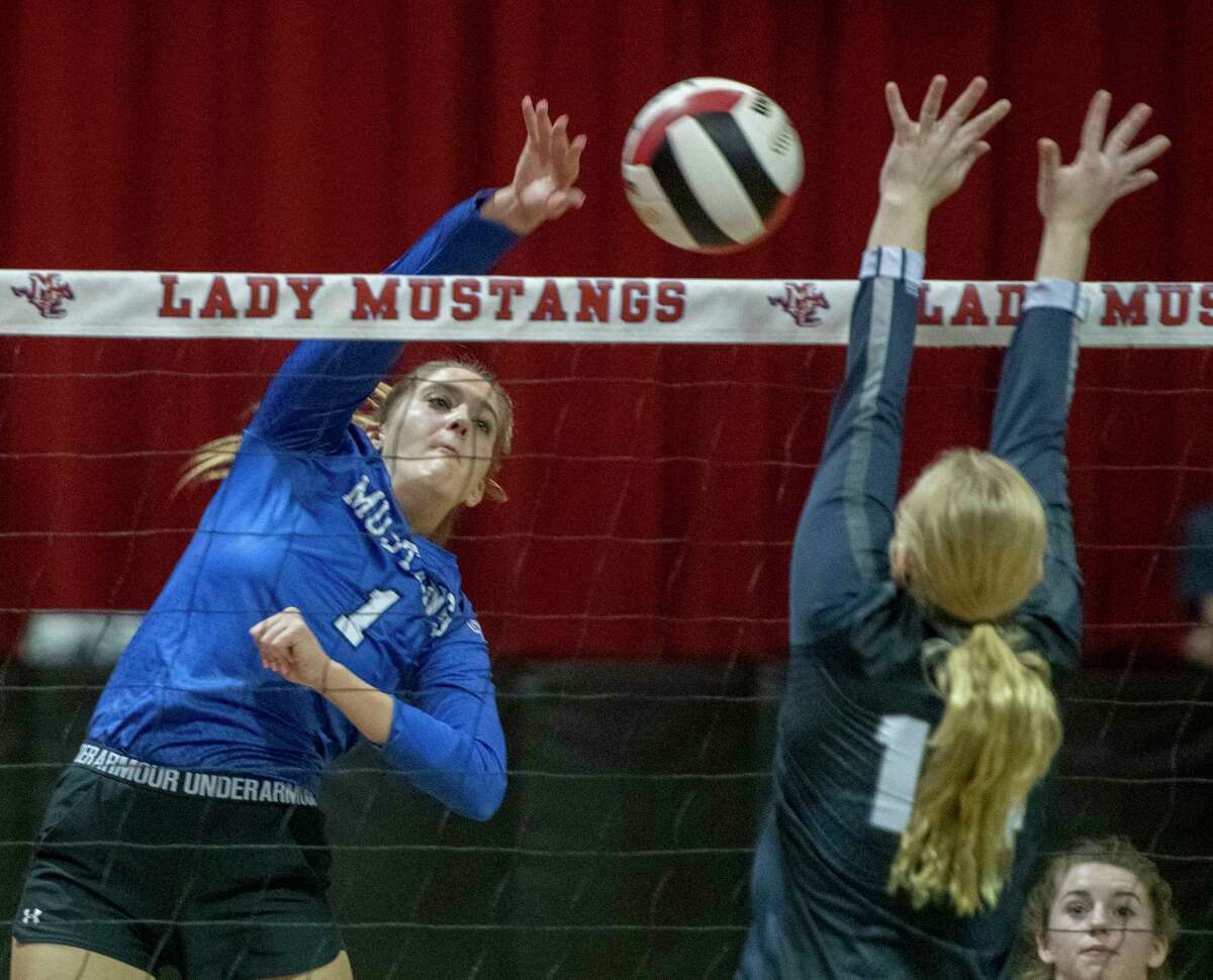 Midland Christian's Ella Sheppard looks for a kill as Liberty Christian's Kaley Janusek goes for a block 10/09/2021 at McGraw Event Center. Tim Fischer/Reporter-Telegram