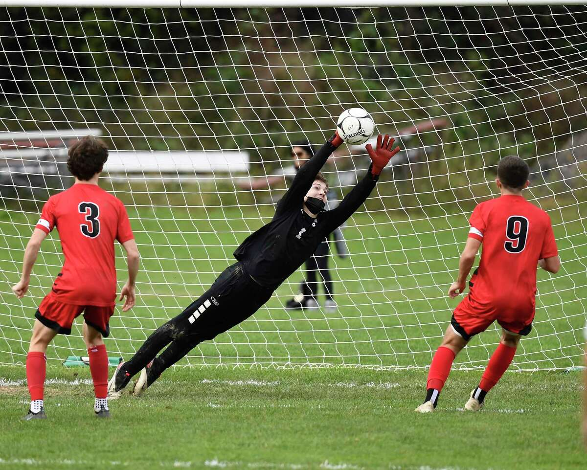 Mechanicville goalkeeper Dylan Raucci makes a save against Guilderland's Sam Tanner (3) and Quin Tynan (9) during the first half of a high school soccer game Saturday, Oct. 9, 2021, in Guilderland, N.Y. (Hans Pennink/Special to the Times Union) ORG XMIT: 101021_bsoccer_HP101