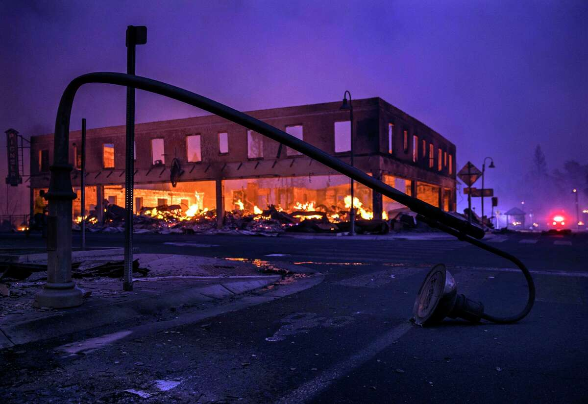 A damaged streetlight lies near Highway 89 and Main Street in Greenville (Plumas County) during the Dixie Fire in August.