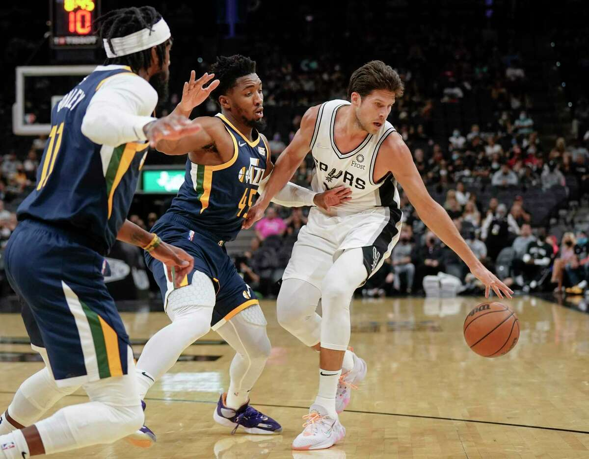 San Antonio Spurs' Doug McDermott, right, drives against Utah Jazz's Donovan Mitchell (45) and Mike Conley during the first half of a preseason NBA basketball game on Monday, Oct. 4, 2021, in San Antonio. (AP Photo/Darren Abate)