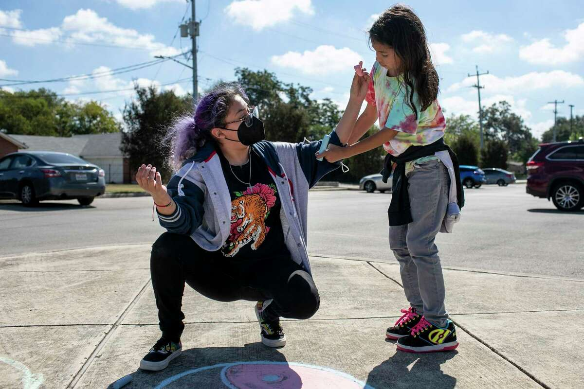 Skyler Castro, 9, helps her big sister, Trinity Castro, 15, roll up her sleeves as Trinity creates a sidewalk mural at Carver Library during Art Pace's annual Chalk It Up event.