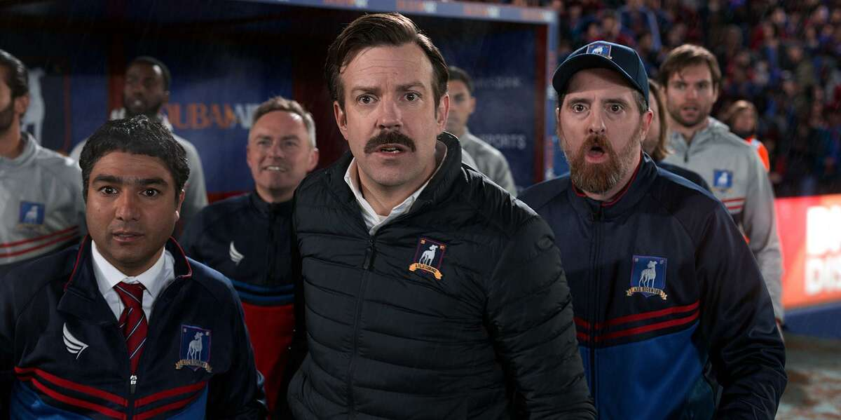 """Jason Sudeikis, center, plays the title character in """"Ted Lasso."""" He stars with Nick Mohammed, left, and Brendan Hunt. (Apple TV+/TNS)"""