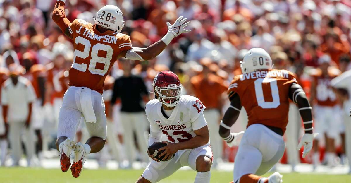Caleb Williams #13 of the Oklahoma Sooners is forced to scramble under pressure by Jerrin Thompson #28 of the Texas Longhorns and DeMarvion Overshown #0 in the second half during the 2021 AT&T Red River Showdown at Cotton Bowl on October 09, 2021 in Dallas, Texas. (Photo by Tim Warner/Getty Images)