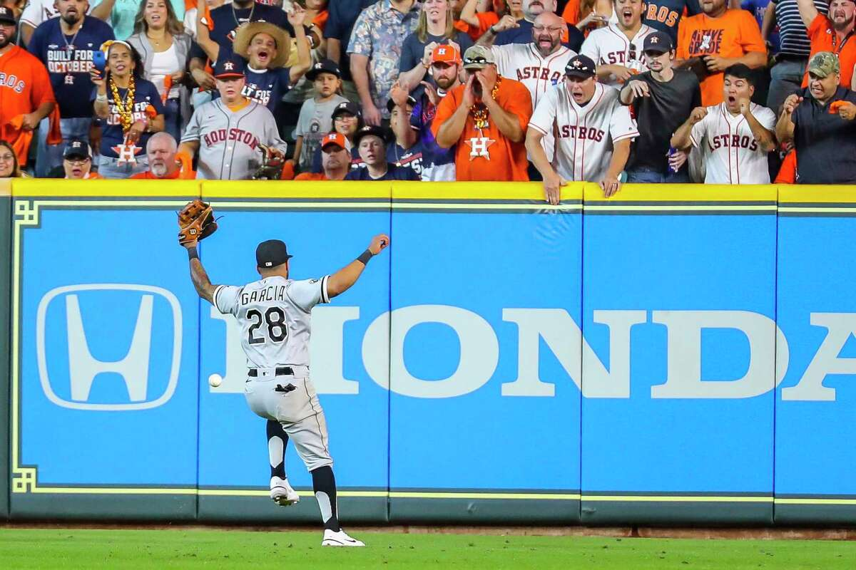 Chicago White Sox right fielder Leury Garcia (28) misses a double by Houston Astros shortstop Carlos Correa (1) that drove in two runs and gave the Astros a 7-4 lead during the seventh inning in Game 2 of the American League Division Series on Friday, Oct. 8, 2021, at Minute Maid Park in Houston.