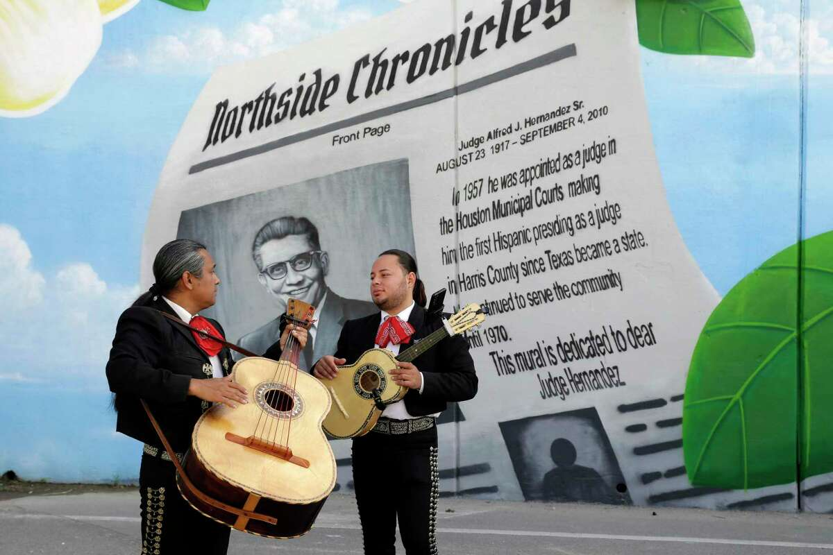 Pablos Solis, left, and Emmanuel Sequeira, right, chat between performances next to one of the mural panels during an unveiling ceremony of the new mural at the tunnel entrance honoring Judge Alfred J. Hernandez, the first Hispanic judge in Harris County, Saturday, Oct. 9, 2021 in Houston, TX.