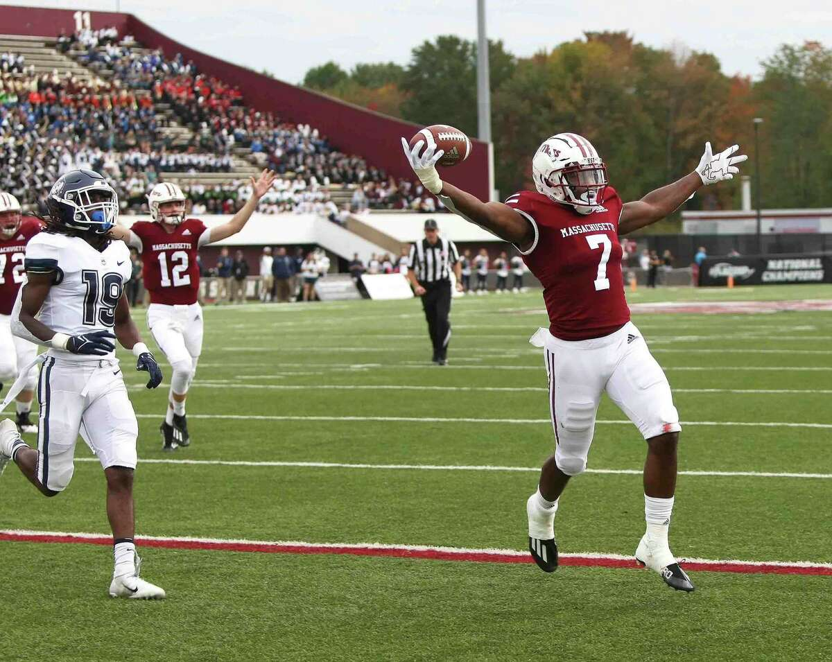 UMass quarterback Brady Olson (12) signals touchdown as Ellis Merriweather runs into the end zone in the first quarter against UConn on Saturday in Amherst, Mass.