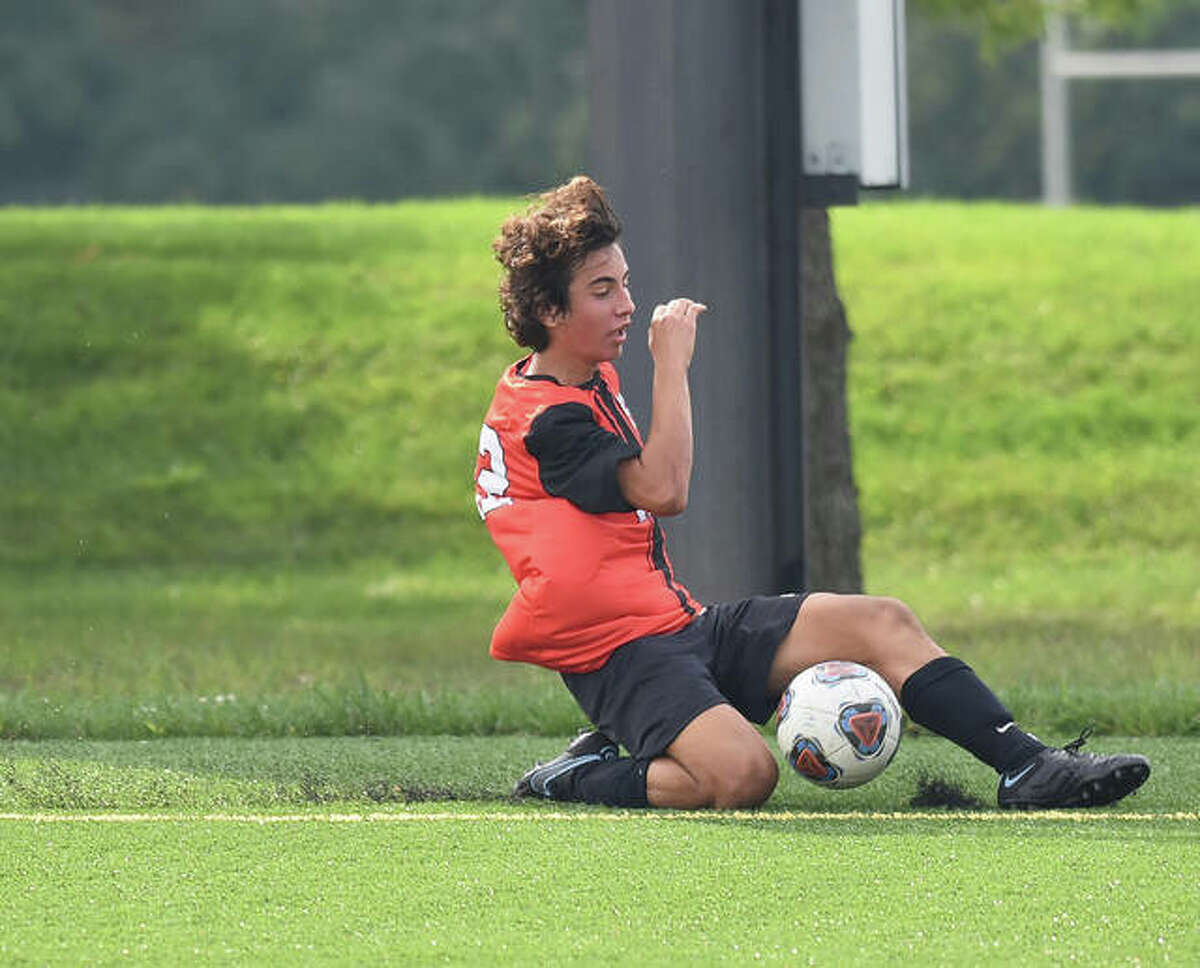 Edwardsville's Abe Giannaris attempts to save the ball from going out of bounds during the first half. Web Gallery